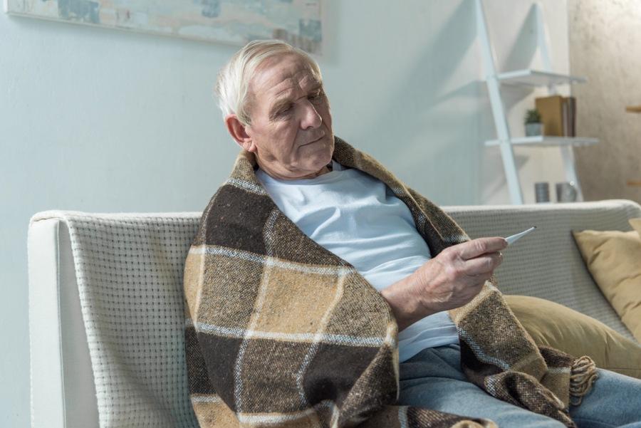 elderly man with Lyme disease and autoimmune disease taking his temperature