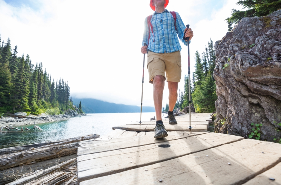 man hiking in shorts along lake
