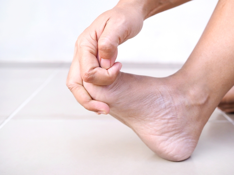person with neuropathy due to lyme disease rubbing their foot