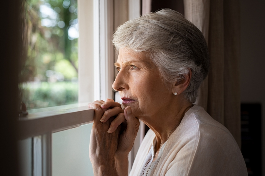 Sad woman with Lyme disease and lewy body dementia looking out the window.