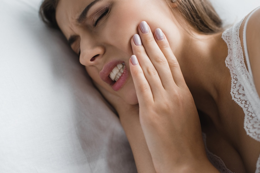woman with TMJ from Lyme disease holding her jaw